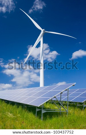 Solar panels and wind turbine against deep blue sky with clouds