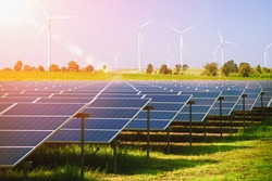 solar panels and wind turbines generating electricity in power station green energy renewable with blue sky background, Natural resource conservation concept. - Image