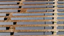 Solar panels farm on the desert aerial view from above. Alternative energy, ecology power conservation concept.