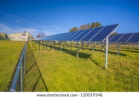 Solar panels in field with blue sky used to furnish electricity to building