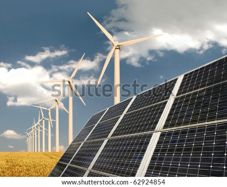 Solar panels in front of wind energy plants and wheat field