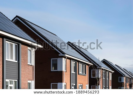 Solar panels mounted on the roofs of a row modern new-build houses in a street in Lemmer, Friesland, the Netherlands with sun and blue sky. Sustainable energy