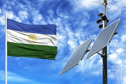 Solar panels on a background of blue sky with a flagpole and the flag of Bashkortostan