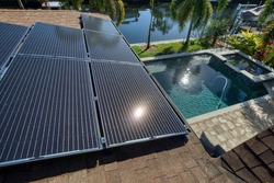 Solar panels on a roof in Florida with view of a pool and a canal.