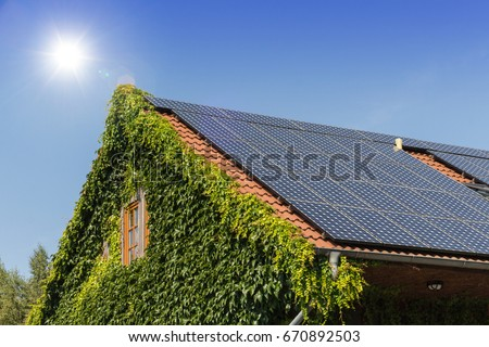 solar panels on a roof with blue sky and sun #670892503