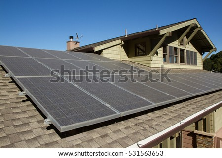 solar panels on roof of house. horizontal orientation, blue sky, gray panels on brown roof. #531563653
