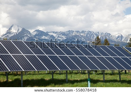 Solar panels on solar power station in Slovakia. Snow covered mountains and white clouds in the background. Green and environmentally friendly sources of energy. #558078418