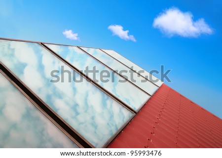 Solar panels on the red house roof with blue sky and clouds