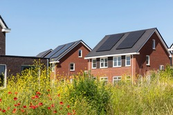 Solar panels on the roof of new built houses in The Netherlands collecting green energy from the sun in a modern and sustainable way. New technology on Dutch houses surrounded by nature, poppy flowers