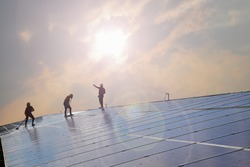 Solar panels or photovoltaic panels installed on the roof of the building which were washing the surface by workers to get high quality and use green and clean energy inside the building below.