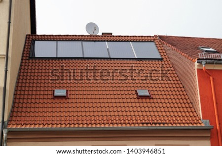 solar panels with satellite dish on the roof of a tiled building #1403946851