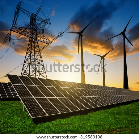 Solar panels with wind turbines and electricity pylon at sunset. Clean energy concept.