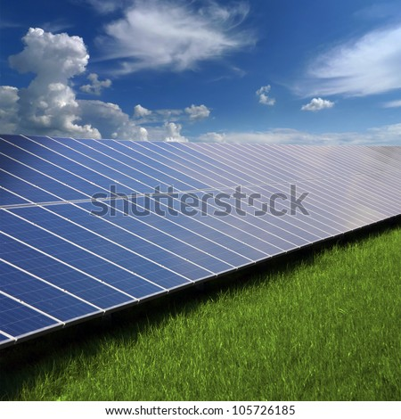 Solar photovoltaic cell panels on green grass under blue sky