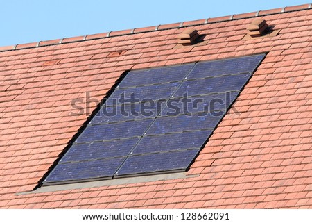 Solar photovoltaic panel array on roof - stock photo