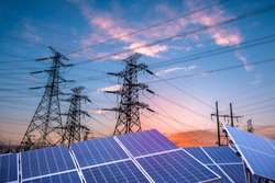 Solar photovoltaic panels and transmission towers at sunset. Alternative power sources - the concept of sustainable resources
