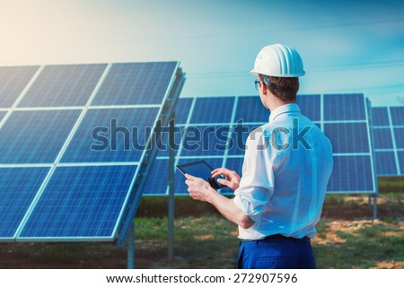 Solar power plant. Engineer with tablet computer on a background of photovoltaic panels. Science solar energy.