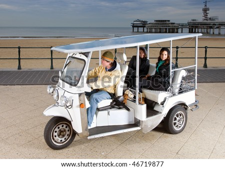 Solar powered tuc tuc at the beach, picking up two young women