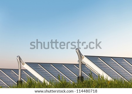 Solar water heating system on grass with an orange blue sky in the background