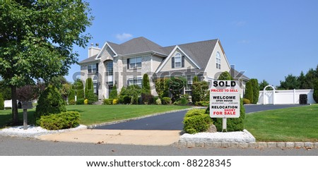 Sold Relocation For Sale Sign on Front Yard Landscape Area of Suburban Brick McMansion Home in Residential Neighborhood on Sunny Blue Sky Day