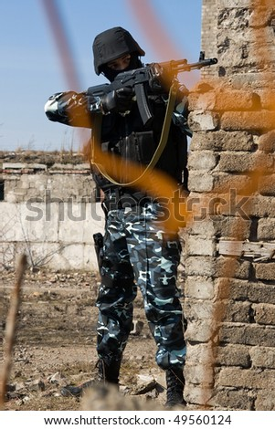 Soldier aiming target with automatic russian AK-47 rifle