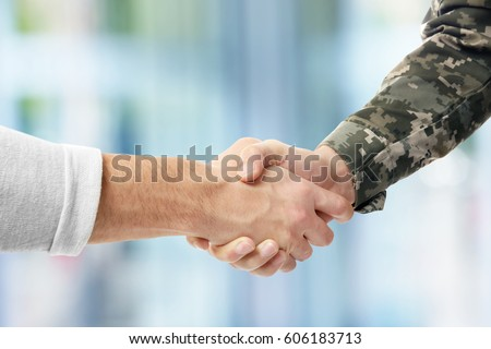 Soldier and civilian shaking hands on blurred background ストックフォト ©
