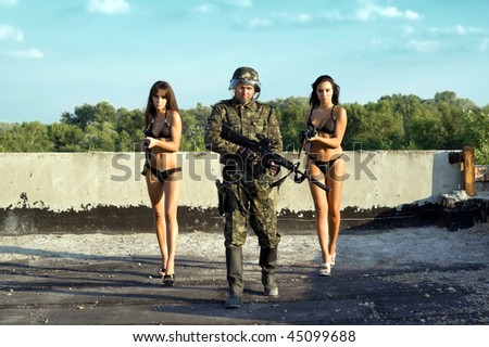 Soldier and two women in underclothes with rifles