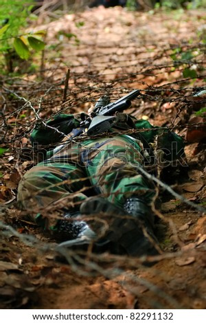 soldier carrying m16 crawling under barb  in combat training