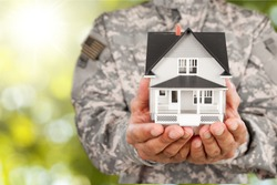 Soldier Holding a Model of House