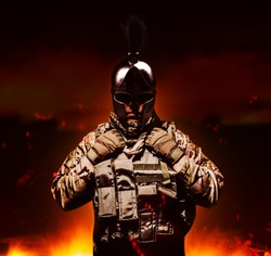Soldier in armored vest and ammunition standing on burning land background in ancient spartan helmet.