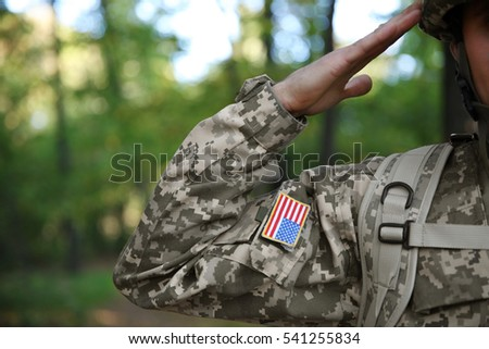 Soldier in camouflage taking salute, close up view