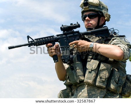 Soldier in camouflage uniform aiming his rifle