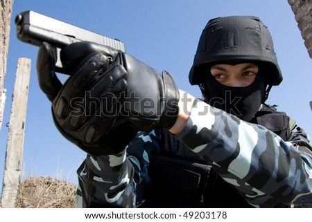 Soldier in full ammunition aiming the target with a semi-automatic 9mm glock pistol