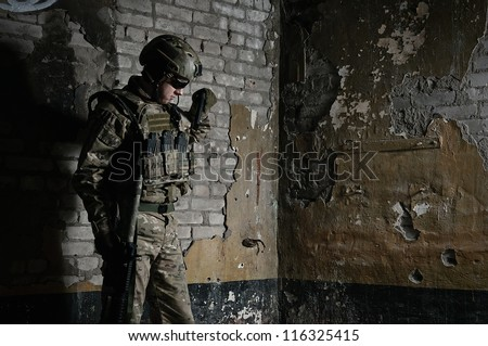 soldier in full gear. against a brick wall. Reloading.