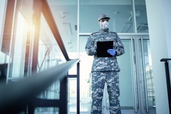 Soldier in military camouflage uniform with rubber gloves and mask guarding in front of hospital's door and controlling who gets in and out. Military helping in fight against coronavirus or COVID-19.
