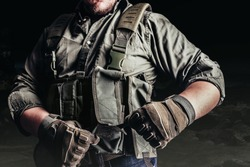 Soldier in tactical outfit and gloves putting on protective armor vest.