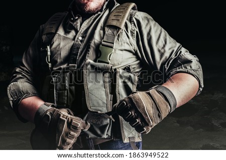 Soldier in tactical outfit and gloves putting on protective armor vest.  Stock photo ©