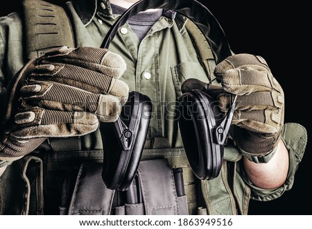 Photo of  Soldier in tactical outfit with body armor, gloves and shirt holding shooting earmuffs on black background.