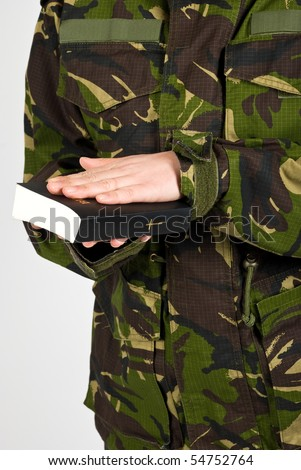Soldier in the army swear with hand on bible to defend the country isolated on white background