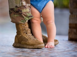 Soldier in uniform and baby at his feet