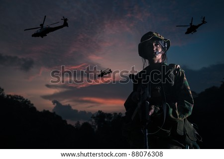 soldier looking victorious with apache helicopter fly past
