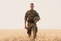 Soldier man standing against a field. Portrait of happy military soldier in boot camp. US Army soldier in the Mission. war and emotional concept.