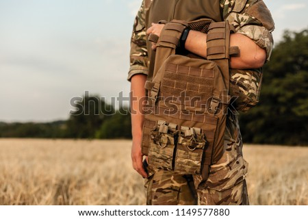 Soldier man standing against a field. Soldier in military outfit with bulletproof vest. Photo of a soldier in military outfit holding a gun and bulletproof vest on orange desert background.