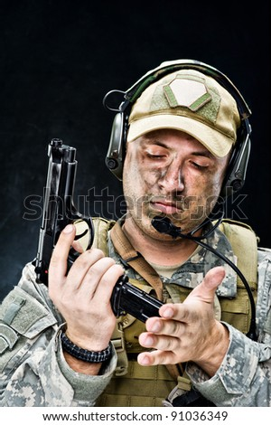 Soldier of USA army posing with a gun on a black background