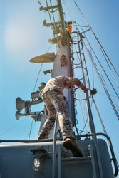 Soldier on the mast of ship.