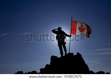 Soldier on top of the mountain with the Canadian flag