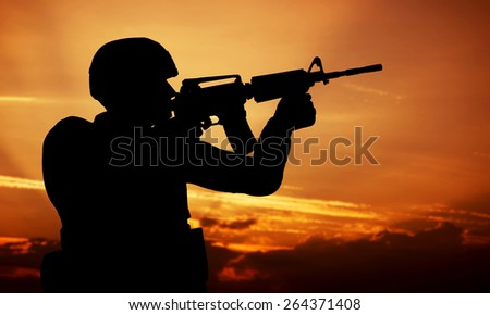Soldier shooting with his weapon, rifle at sunset. War, army, military.