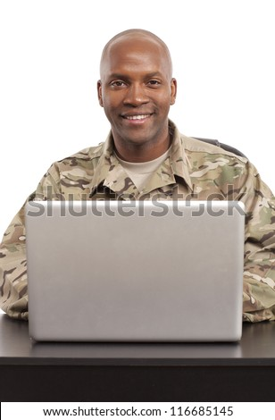 Soldier smiles while working on a computer