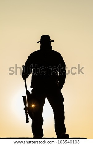 soldier standing in the sun with a rifle resting with the flash of the sun - stock photo
