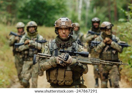 soldier stands with arms together with other