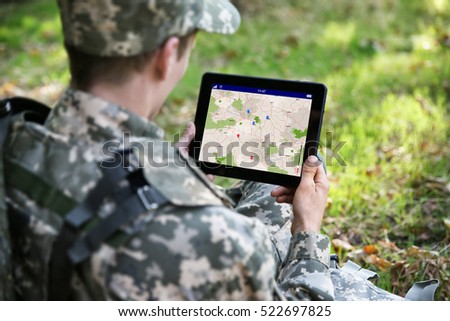 Soldier using map on tablet for orientation at forest ストックフォト ©
